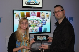Katy and StealthBuda holding a black Wii U GamePad showing the Nintendo Land game select screen in the background